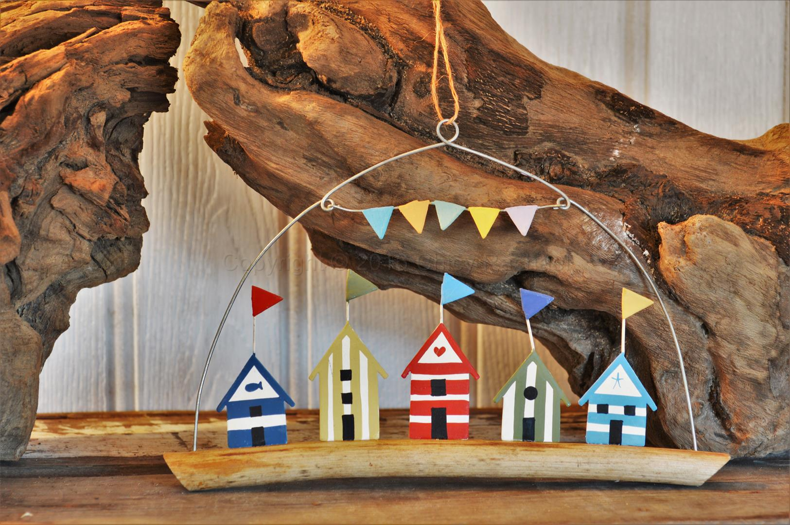 Five Coloured Beach Huts On Driftwood