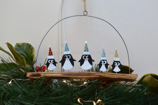 Penguins In Spotty Hats On Driftwood